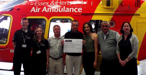 Former airlifted patient Steve Barker with his family at Essex & Herts Air Ambulance's North Weald Airbase with members of his family, Bishop's Stortford Golf Club and Charity Staff
